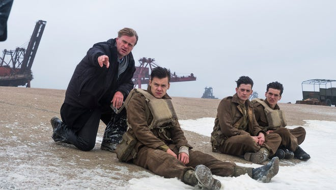 Christopher Nolan talks to his young 'Dunkirk' soldiers (from left) Harry Styles, Aneurin Barnard and Fionn Whitehead.