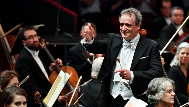 Langree goes into the orchestra to thank soloists at The Proms in Royal Albert Hall.