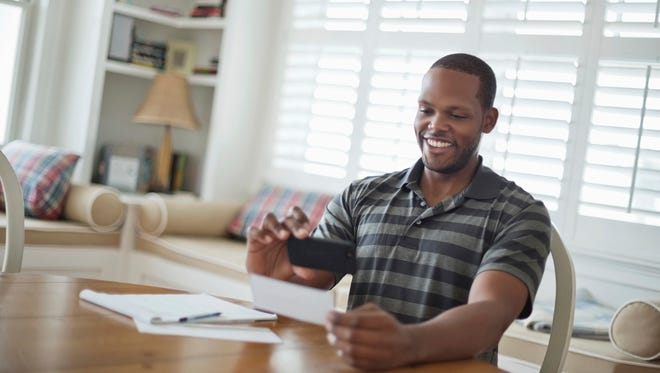 Mid adult man using mobile phone to deposit check at home