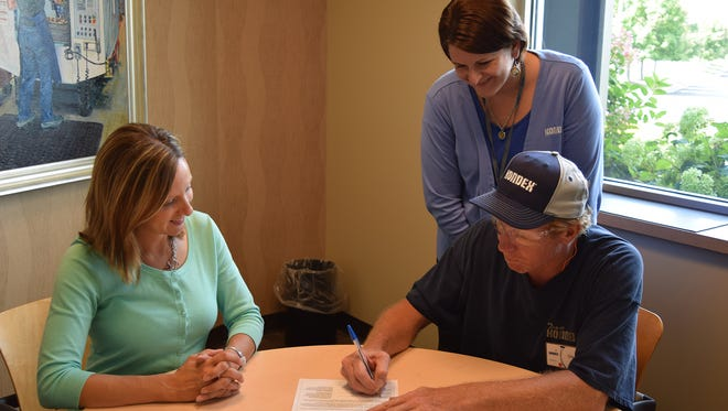 Kondex Maintenance Technician II Chad Reinke signs a contract formalizing his participation in a Maintenance Mechanic Apprenticeship, and is joined by State of Wisconsin Apprenticeship Training Representative Elizabeth Pusch (left) and Kondex HR Representative Kelly Peterson.