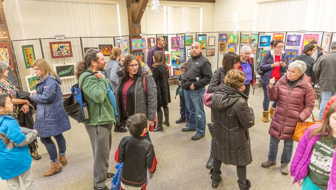 Adults and children examine the works of young artists at the Children's Environmental Art Show at the Environmental Education Center from Friday, Jan. 5, to Sunday, Feb. 4.