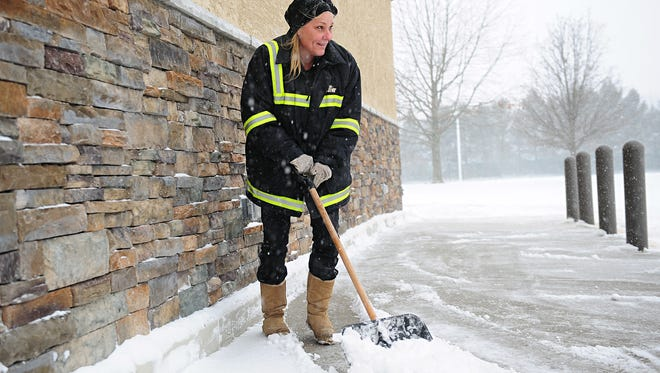 Wawa employee Teresa shovels snow at the East Chestnut Avenue location in Vineland as heavy snow falls Thursday morning.