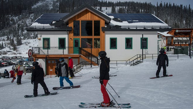 Skiers and snowboarders glide past the Kids' Center with solar panels affixed to the roof on Thursday, Jan. 11, 2018, at Arapahoe Basin Ski Area in Keystone, Colo.