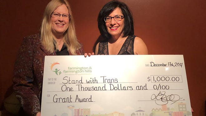 Lynn Halton, Trustee of FFHFYF, presents a grant award check to Roz Keith, President of Stand with Trans.