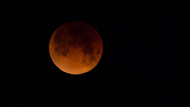 The Super Blood Blue Moon takes on a red hue during the total lunar eclipse on Wednesday morning, Jan. 31, 2017, at Horsetooth Reservoir in Fort Collins, Colo.