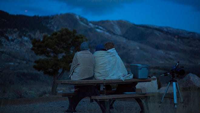 From left, Jessica Blohm, Blaine Zewdu and Cecily Meade huddle together under blankets while watching the Super Blood Blue Moon set on Wednesday morning, Jan. 31, 2017, at Horsetooth Reservoir in Fort Collins, Colo.