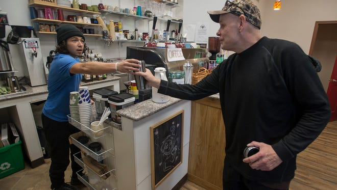 Barista Benjamin Euresti hands back Matthew Stringer's cup after topping it off with hot water on Wednesday, Jan. 31, 2017, at LoCo Artisan Coffee House in Loveland, Colo.