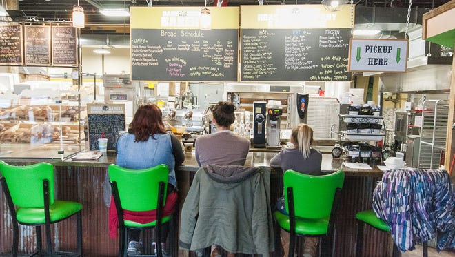 A group sits at on the bar stools while waiting for their coffee Friday afternoon at Dark Street Roasting Company and Coffee House.