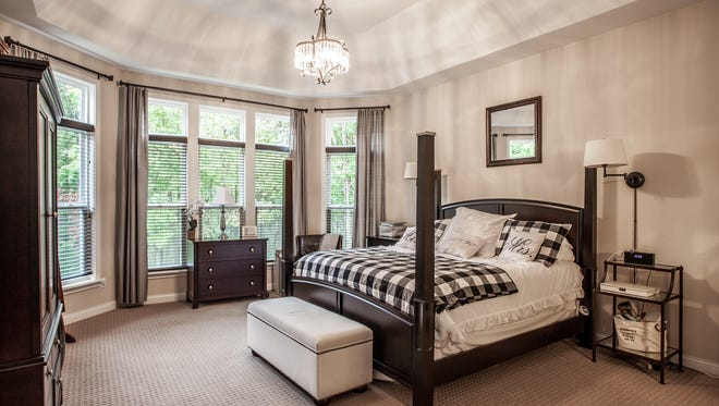 The large master bedroom features tray ceilings and floor-to-ceiling windows.