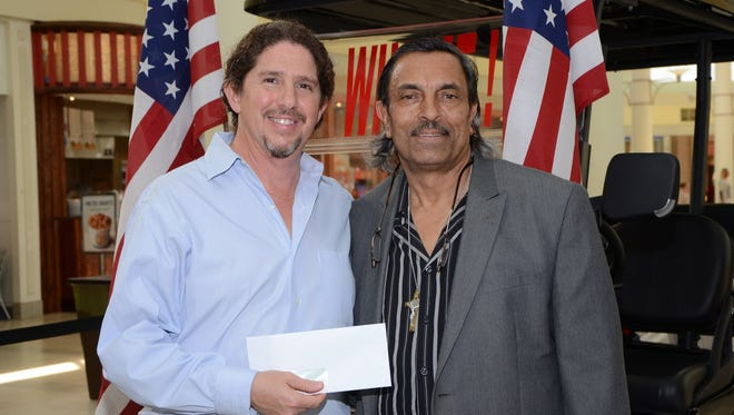 """From left, Peter Wernick, owner of Peter's Water Treatment & Irrigation/Ecowater Systems in Stuart, presents Bienvenido """"Rubén"""" Ottenwalder with a $10,000 check for winning his free sweepstakes."""