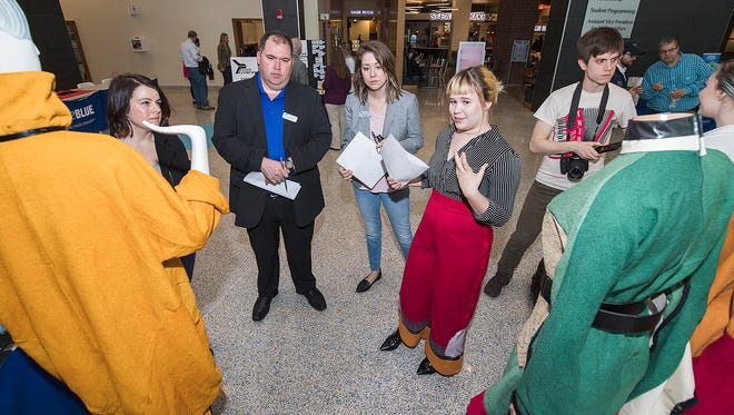 Jones College of Business management faculty Kristine Shanine, left, Dennis Gupta and Kelly Manix listen as MTSU senior Lindsey Engle, right center, explains her business plan during the March 28 Student Trade Show preliminary competition held in the Student Union Atrium.