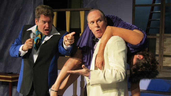 """Rhett Pennell, as a Broadway actor who plays Sherlock Holmes, gives instructions to fellow thespian Dusty Ray on what to do with a deceased dinner guest, played by Liz Keimer, during """"The Game's Afoot,"""" which opens April 27 at Surfside Playhouse."""