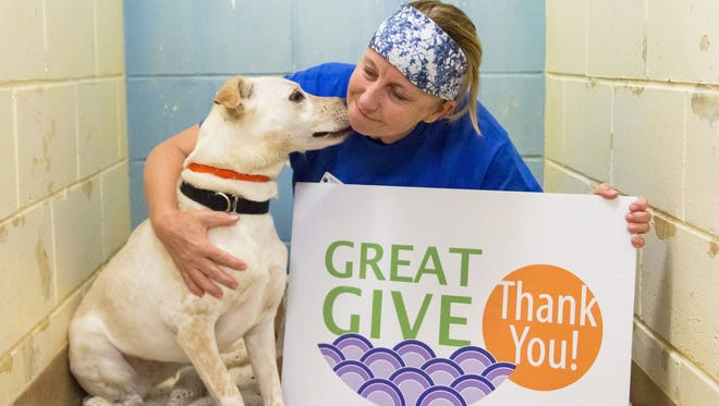 Sandi Banks gets some love from one of the shelter dogs as they both give thanks to donors for their generosity during the Great Give.