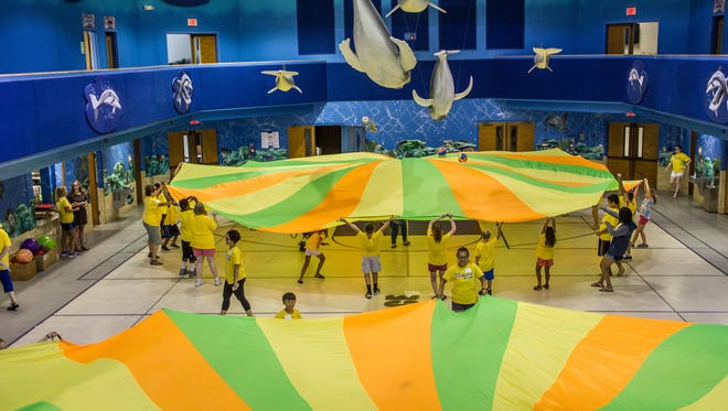 Every activity at Camp Fearless has a purpose.  Children here are playing the parachute game, which practices team building and relying on others.