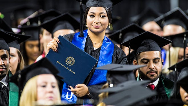 A recent MTSU graduate shows off her diploma during the August 2018 commencement ceremony in Murphy Center.