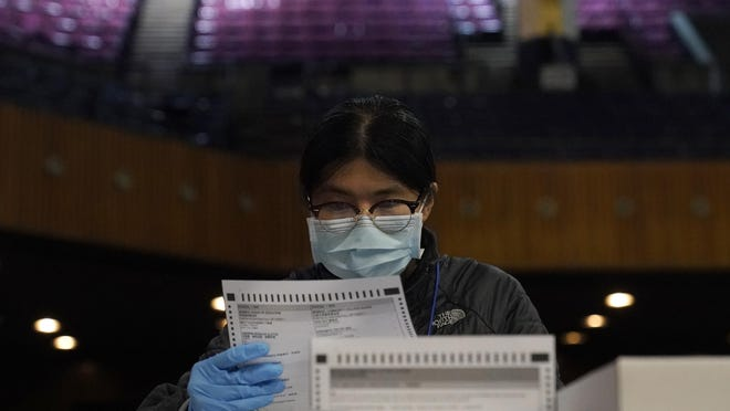 San Francisco Department of Elections worker Rosy Chan checks for damaged ballots at a voting center in San Francisco, Sunday, Nov. 1, 2020.
