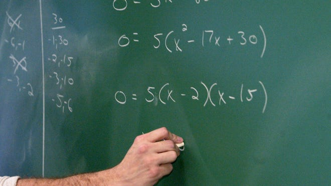 A teacher writes algebraic equations on a classroom chalkboard. /Charlie Nye / The Star 2003 file photo