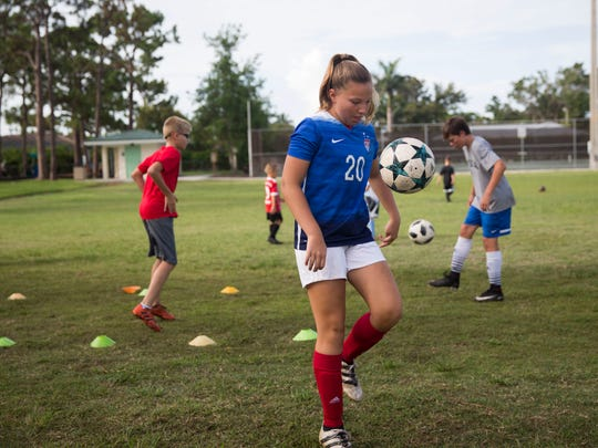 Josephine Vickaryous, age 12, juggles a soccer ball during Kick-Off Soccer's summer day camp at the Seagate Park in Naples Friday, June 15, 2018.