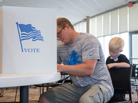 fills out his ballot during the South Dakota School