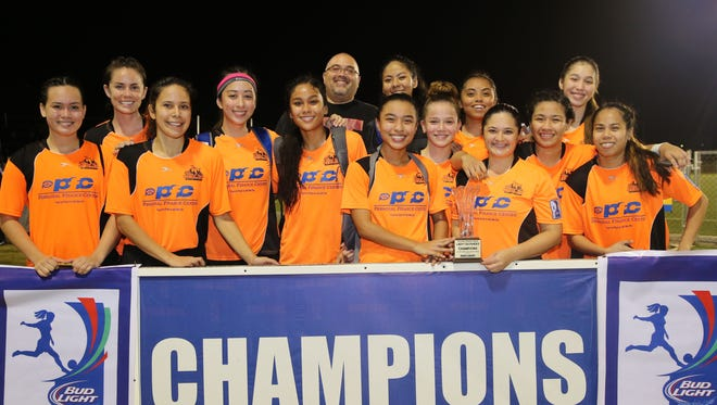 The Personal Finance Center Lady Crushers pose for a team photo with the championship trophy of the Bud Light Women's Soccer League Premier Division (W1) after winning the final 4-2 against Quality Distributors Sunday at the Guam Football Association National Training Center. In the photo, from left to right, are Colleen Naden, Katie Wendal, Anjelica Perez, Demie Rose Brennan, Kaeliana Taitano, Ambros Marketing Manager Jojo Camacho (in back), Skyylerblu Johnson, Aeryn Anulao (behind Johnson), Samantha Fegurgur, Brittany Meno, Carla Haddock, Caylani Estoy, Elysia Perez, and April Talledo.