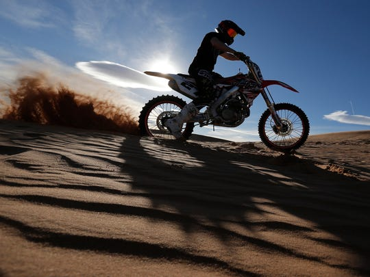 Travis Waters rides the dunes at Red Sands Sunday afternoon. The county is considering closing the popular recreation area to the public.