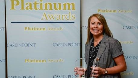Meridian Health Services Director of Primary Care Jennifer Henderson holds the two Decision Health Platinum Awards recently awarded to Meridian.