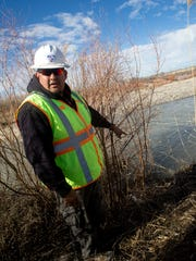 Gregory Bahe, operations supervisor for water and wastewater in the engineering, construction and operations division at Navajo Tribal Utility Authority, points out an area where wastewater is leaking into the San Juan River on Dec. 21.