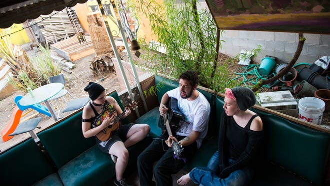 """Joa Fischer (left to right) and Kameron Fein play and guitar and sing along with Nemo Nelson before the memorial service for """"Krazy Bill"""" Krist at The Sp(a)ce on June 26, 2015."""