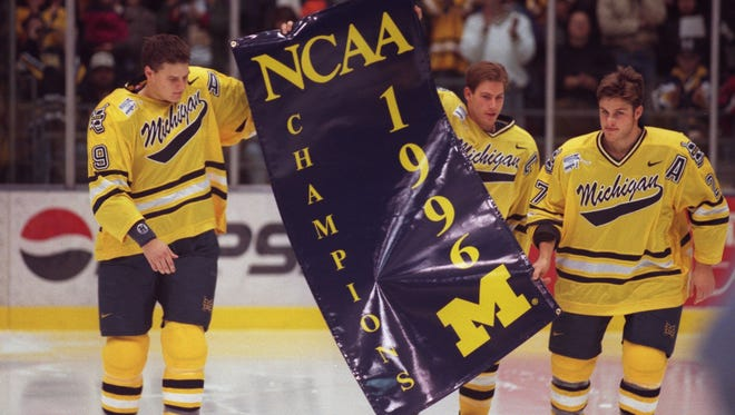 The Michigan hockey players Jason Botterill, Brendan Morrison and 27 Blake Sloan bring the NCAA championship banner into Yost Ice Arena.