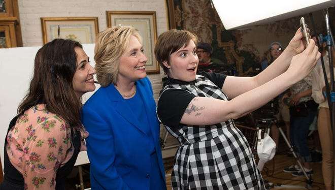 Lena Dunham, right, poses for a selfie with Hillary Clinton (center).