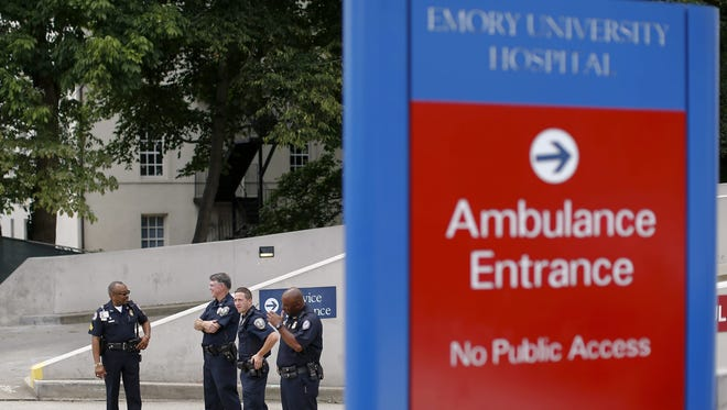 Police officers stand guard after an ambulance transporting Kent Brantly, who was infected with the Ebola virus, arrived at Emory University Hospital in Atlanta in August.
