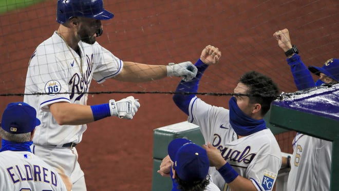 Kansas City Royals' Ryan McBroom, top left, is greeted by teammates after his solo home run in the sixth inning Friday night against the Minnesota Twins at Kauffman Stadium in Kansas City, Mo.