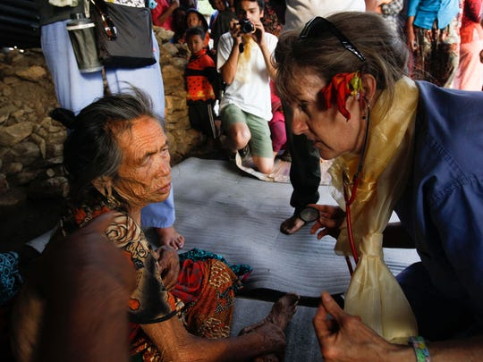 Delaware Medical Relief Team member Deirdre Ritchie examines a wound that Dun Mayay Tomang suffered during a 7.8-magnitude earthquake in Nepal April 25.