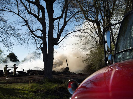 The Lynnville Fire Department continues putting water on the remains of a house that burned to the ground on Hwy 61 south of Lynnville, Ind., Monday afternoon. It was earlier thought a dog and cat had perished in the fire, but the dog was later found in a pen in the backyard.