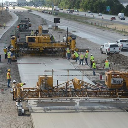 Construction crews lay fresh concrete on northbound