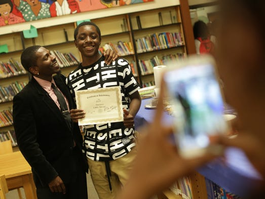 Eighth-grade teacher Olafemi Bankole Akintunde congratulates