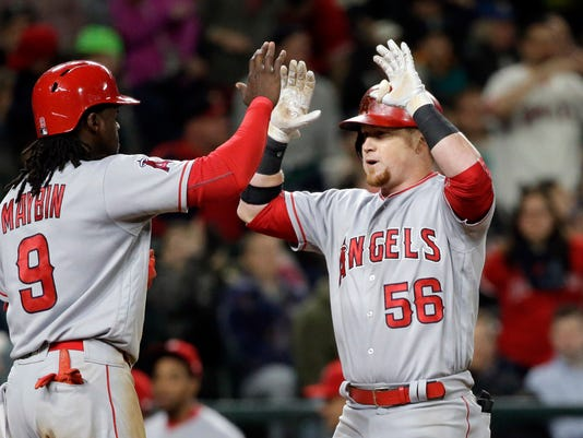 Los Angeles Angels' Kole Calhoun (56) is met at home by Cameron Maybin on Calhoun's two-run home run against the Seattle Mariners during the eighth inning of a baseball game Tuesday, May 2, 2017, in Seattle. (AP Photo/Elaine Thompson)