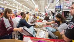 Customers go through sheet sets at Walmart's Black