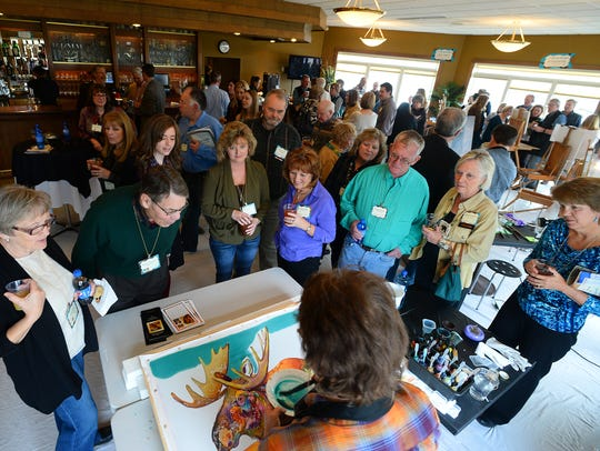 Nancy Dunlop Cawdrey draws a crowd during the Art in Action quick finish event at Meadow Lark Country Club during the 2016 Western Art Week.