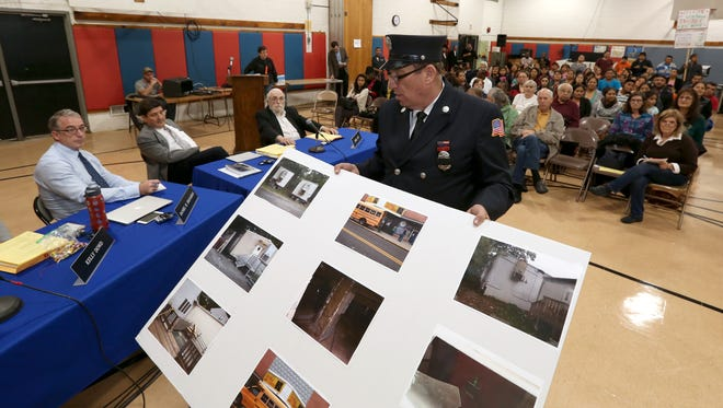 Justin Schwartz of the Spring Valley Fire Department and a member of the illegal housing task force presents photos of fire violations at yeshivas during an October 2015 East Ramapo school board meeting.