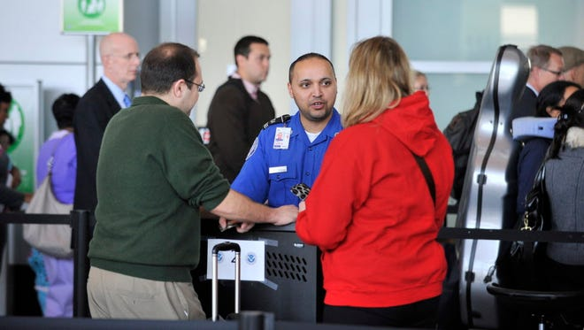 A Transportation Security Administration officer talks with travelers Oct. 7, 2011, at Boston Logan Airport.