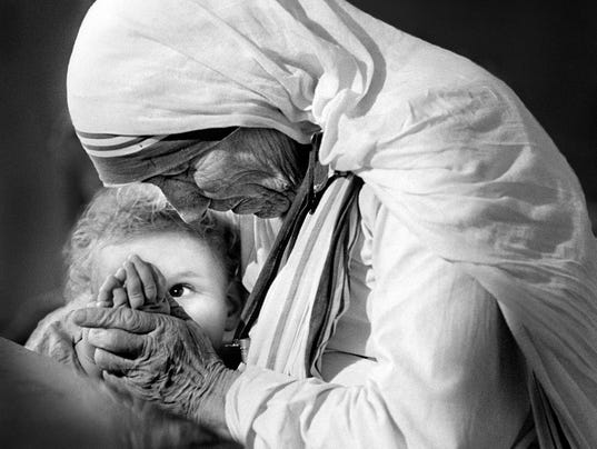 32_Mother and Child--Mother and Child—Mother Teresa was speaking at a press conference when this small child interrupted her for a moment.  Mother Teresa grabbed the child and brought her in close to say a little prayer with her.