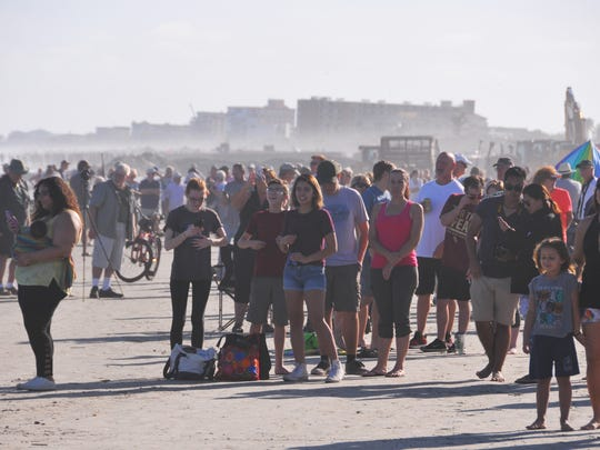 Crowds of people. reminiscent of shuttle launch days, line the beaches of Cape Canaveral and Cocoa Beach to watch the  launch of the SpaceX Falcon Heavy from Pad 39A at Kennedy Space Center and the return of the rocket's boosters landing at Landing Zone 1 and 2 at Cape Canaveral Air Force Station.