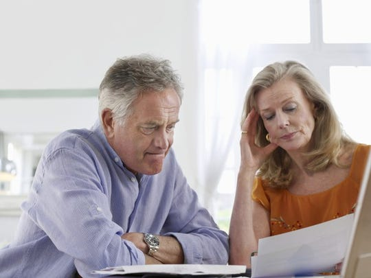 A worried couple mulling over their finances.