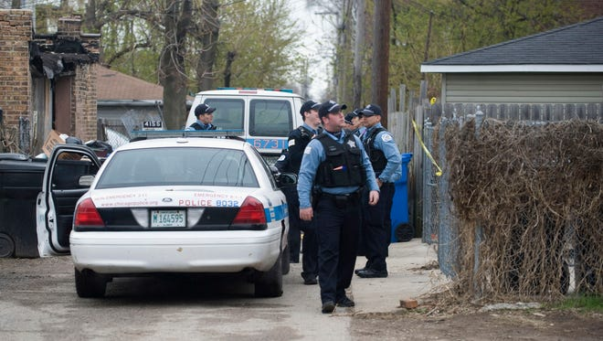 Police stand outside a residence in Chicago Monday after a 14-year-old girl was fatally shot and another girl wounded in the Back of the Yards neighborhood in Chicago.