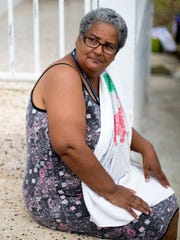 Marta Rodriguez, 54, sits on her neighbor's stoop in
