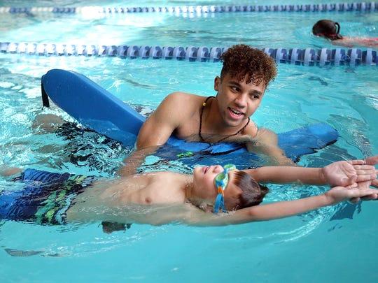 Mason Sine teaches Cadel Laborda how to swim at Fairmont Aquatic Center in Salt Lake City on Tuesday, May 22, 2018.