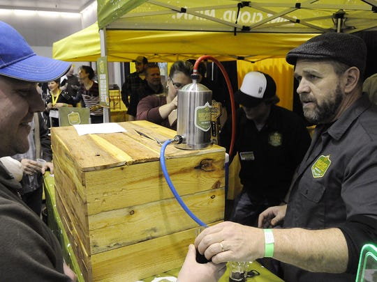 Greg Knoll serves a sample Jan. 24 at the Beaver Island Brewing Co. booth at the 2015 St. Cloud Craft Beer Tour.