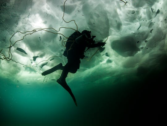 Diver Rich Synowiec heads under the ice in Lake Erie,