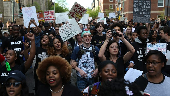 """Students from Baltimore colleges and high schools march in protest April 29, chanting, """"Justice for Freddie Gray"""" on their way to City Hall. Baltimore remains on edge in the wake of the death of Freddie Gray, though the city has been largely peaceful following a day of rioting this past Monday. Gray, 25, was arrested for possessing a switch blade knife April 12 outside the Gilmor Houses housing project on Baltimore's west side. According to his attorney, Gray died a week later in the hospital from a severe spinal cord injury he received while in police custody."""